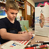 BRYAN EATON/Staff photo. Students in Kristen Mollineaux's class at Newbury Elementary School have been making gifts for parents in art class and regular classroom time. This week they decorated the bags they put them in, Sam Harding, 7, using NFL designs, he being a Buffalo Bills fan and will be seeing family there on Christmas.