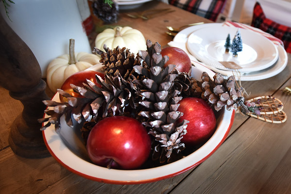 BRYAN EATON/Staff photo. Items as simple as pine cones and apples accent the dining room table.