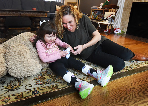 BRYAN EATON/Staff photo. Robbie Edwards, 4, with her mom, Kasey in their Newburyport home. Robbie is believed to be one of only 17 people globally with the disease spastic paraplegia-47, a neuro-degenerative condition without a cure.