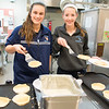 JIM VAIKNORAS/Staff photo Bridget Sheehan and Olivia Ritchie serve pancakes at the annual Newbury Elementary School Holiday Bazaar and Breakfast Saturday morning. Along with pancakes, there was a raffle , bake sale and a visit from Santa .