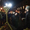 BRYAN EATON/Staff Photo. Ruby Latham, 11, of Newburyport assists Ahavas Achim Congregation leader Alex Matthews light the menorah in Newburyport's Market Square for the second night of Hanukkah on Monday.