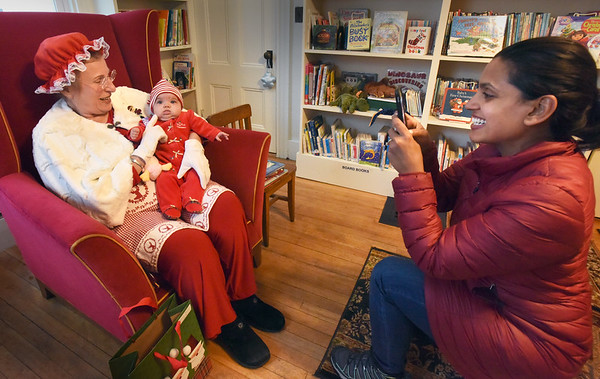 BRYAN EATON/Staff Photo. Sarah Foley of Andover takes a photo of her daughter, Naiomi Jean Foley, four months, at the Emma Andrews Library and Community Center while on a visit to the baby's great-grandmother Jean Doyle of Newbury. Youngsters got to meet Mrs. Claus, played by Jeanette Isabella, heard some stories, did some coloring and had cookies and hot cocoa.