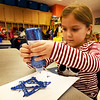 BRYAN EATON/Staff Photo. Kenzie Medeiros, 6, puts blue sparkle on a Star of David ornament she made in Linda Gershuny's class at the Bresnahan School in Newburyport. The children were learning about different wintertime holidays around the world and created different ornaments to present to their parents.
