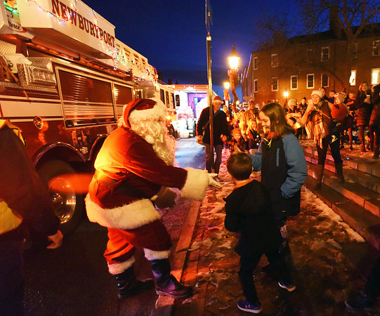 BRYAN EATON/Staff Photo. Jolly Ole St. Nick rode into Market Square in Newburyport on Monday night climbing off the fire truck to greet youngsters in the 47th Annual Santa Claus Parade. The parade was sponsored by the Newburyport police and fire departments, Newburyport Teachers Associaton and Simply Sweet shop.