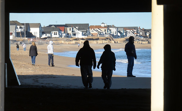 BRYAN EATON/Staff photo. An unseasonably warm Saturday brought people out to Salisbury Beach in a view framed by the pylons of the Blue Ocean Event Center. After a wintry mix today, New Year's Day is sunny and the end of the week warms into the mid-40's though with rain.