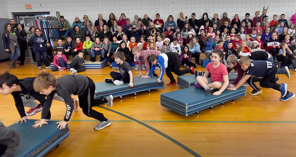BRYAN EATON/Staff Photo. The third-graders heat of the Reindeer Races at Salisbury Elementary School go three loops around the gymnasium, each of the three team members taking turns riding on the matts. One of the more popular school-wide activities of the year the noise is deafening as each class cheer on their teams.