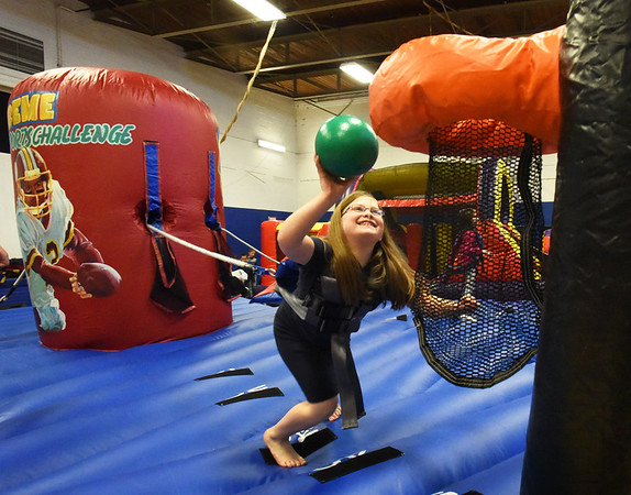 BRYAN EATON/Staff Photo. Harnessed up to a tensioned rope that she has to fight to move forward, Summer Packer, 8, tries to put the ball in the hoop on one of the inflatable extreme sports challenge stations at the Boys and Girls Club on Monday. The club is open for school vacation this week on Thursday and Friday and Monday and Tuesday before New Year's Day.
