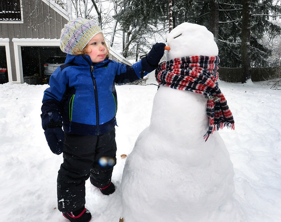 BRYAN EATON/Staff Photo. Snow from the first storm of the season was perfect for making snow forts, snowballs and snowmen as it was sticky.  Lily Veit, 2, puts the carrot nose on her creation she made with her mom, Chaitra, at their Newburyport home.