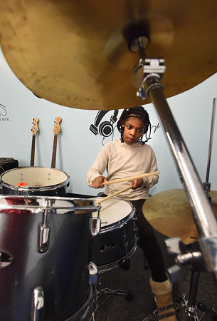 BRYAN EATON/Staff Photo. Lakansyil Gerard, 7, works on her drumming in the music room at the Boys and Girls Club under the direction of Tomas Havrda. The club also teaches guitar and ukelele and for those more vocally inclined they also do karaoke.
