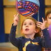 BRYAN EATON/Staff Photo. Blakely Millette, 6, tries to spin a basketball in the style of the Harlem Globetrotters in physical education class at the Bresnahan School on Wednesday afternoon. The youngsters were trying out different tricks with the balls as they worked on agility and eye-to-hand coordination.