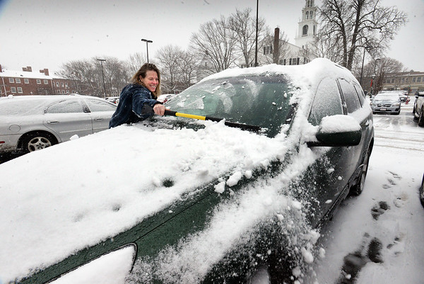 BRYAN EATON/Staff Photo. Newburyport resident Ellen Link cleans off her car in Newburyport's Green Street Lot during the storm that was more of a nuisance than anything major. With the snow sure to melt the forecast for Christmas is it likely won't be white.