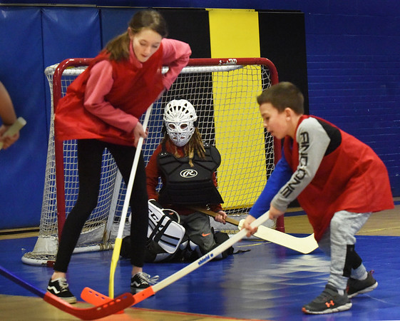 BRYAN EATON/Staff Photo. Goalie Manu Poupon, 9, is at the ready as Grace Wolcik, left, and Jackson Rutherford looks to score a goal at the Boys and Girls Club in Salisbury on Monday. They were holding their 12th Annual Floor Hockey Tournament which has become tradition over Christmas vacation.