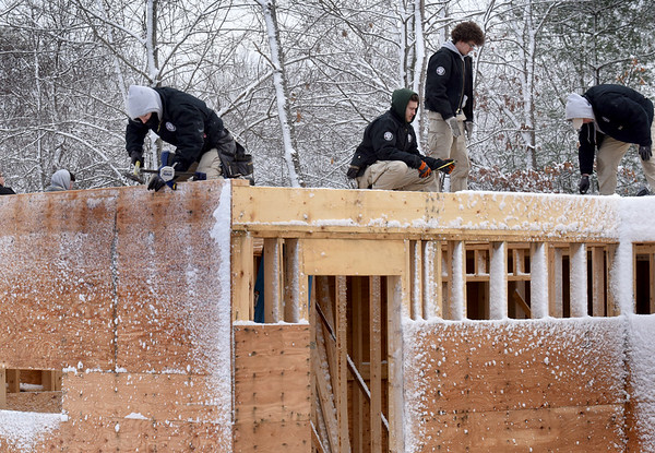 BRYAN EATON/Staff Photo. A crew from Americorps and Whittier Vocational Tech work on a third building for Habitat For Humanity and Old County Road in Salisbury.