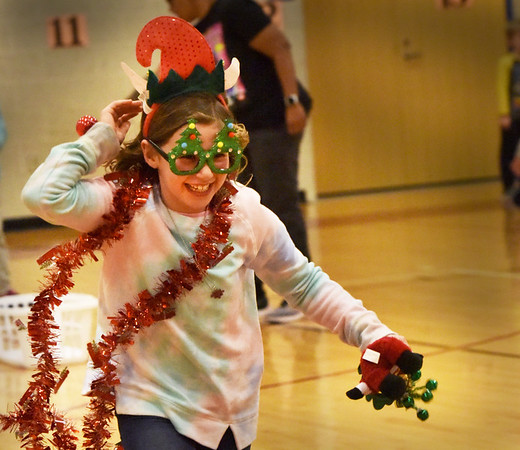 BRYAN EATON/Staff Photo. Tiegan LaFrance, 8, runs in the Santa Relay at the  Greater Newburyport YWCA's Afterschool Program on Monday afternoon. The youngsters had to pull Christmas-theme accesories from a laundry basket, put them on and run to the end of the gymnasium and back for the next team member to compete.
