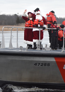 BRYAN EATON/Staff photo. Santa and Mrs. Claus arrive at Newburyport's waterfront courtesy of one of the motor lifeboats of the U.S. Coast Guard Station Merrimack.