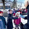 "BRYAN EATON/Staff Photo. Norman Avenue resident Carol Blackburn receives handmade greeting cards and cinnamon scented ornaments from Bresnahan School students, from left, Lark Trainor, 5, Mia Geerlings, 8, and Charlotte Robinson, 8. Kindergartners in Dianna Ouellette's class and third-graders in Nonie Olson's class, which are ""buddy classes,"" went through the Newburyport neigborhood next to the school for the deliveries as they learned about giving, caring, and sharing as being the true gifts of the holiday season and that exchanging kindnesses among friends is a wonderful way to promote ""Peace on Earth."""