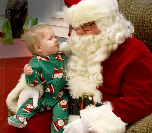 BRYAN EATON/Staff photo. Flynn Brown, 9 months, was a little leery at first when meeting Santa Claus but shortly gave a smile at the Hilton Senior Center in Salisbury on Saturday morning. He was attending Breakfast With Santa sponsored by the Salisbury Fireman's Association. On Sunday night Santa got a ride around town aboard a fire engine waving to youngsters along the route.