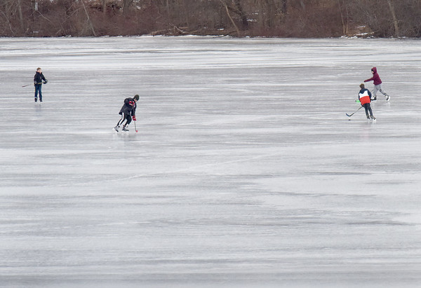 BRYAN EATON/Staff Photo. Youngsters pass around a hockey puck on Lake Gardner in Amesbury just off the beach Thursday morning. Going onto the ice this weekend may have to be reconsidered as the temeratures are warming into the mid-40's.