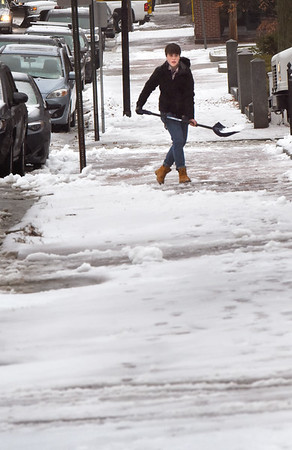 BRYAN EATON/Staff Photo. Mia Yin, 15, shovels off the sidewalk at her State Street, Newburyport home as the precipitation turned to rain on Monday afternoon. The weather starts to warm up on New Year's Day and into the weekend, though rain is in the forecast Friday and Saturday.