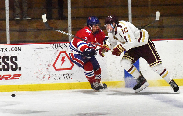 BRYAN EATON/Staff Photo. Ben Reynolds shoots past a Burlington player to get to the puck.
