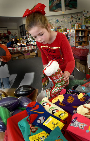 BRYAN EATON/Staff Photo. Bella Eaton, 9, checks out dog toys, among other iterms, at the Salisbury Elementary School's Holiday Shop on Thursday. The event, sponsored by the school's PTA is not a fundraiser, but helps children to organize a list, budget their money and balance different pricing to help them stay within that budget.