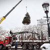 BRYAN EATON/Staff Photo. This year's Christmas Tree is lowered into Market Square in Amesbury late Wednesday morning with the help of a crane temporarily detouring traffic. The tree will be lit after the Amesbury Holiday Day Parade this Saturday which starts at 3:30.