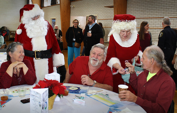 Karen Cameron Photo. The Amesbury Council on Aging held their annual Holiday Luncheon at Holy Family Parish Hall on Thursday as the Rotary of Amesbury served lunch prepared by Shared Living Collaborative with entertainment provided by Dan Cleary and Chuch Wright and the Amesbury High School Rhythmics. Enjoying their time, from left, are Linda Welch, Santa Claus, Raymond Fortier, Mrs. Claus handing Donald Fortier a candy cane.