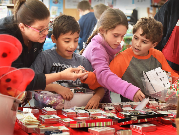 BRYAN EATON/Staff Photo. Librarian Lill Chalifor helps Rafael Galarza, 8, choose a gift for his mother as Savannah Ironfield, 8, and Liam Medina, 8, choose items for their family members at the Salisbury Elementary School's Holiday Shop on Thursday. The event, sponsored by the school's PTA is not a fundraiser, but helps children to organize a list, budget their money and balance different pricing to help them stay within that budget. The PTA hopes to break event in the annual event and was given a discount on the items by the Salisbury Discount House.