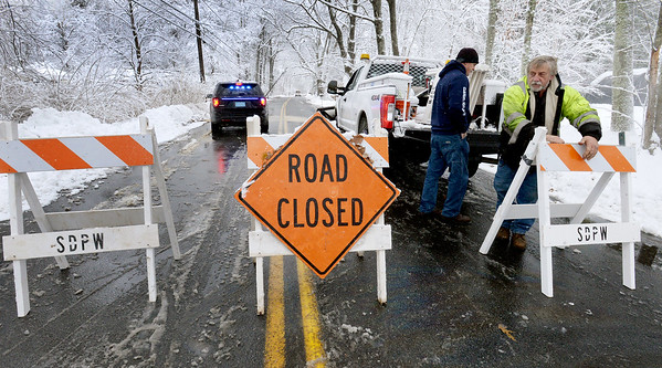 BRYAN EATON/Staff Photo. Salisbury DPW highway foreman Ray Cote, right, and Linwood White put up signs on Folly Mill Road while an electric crew was on the way to deal with a utility pole was tilted from snow on the wires.