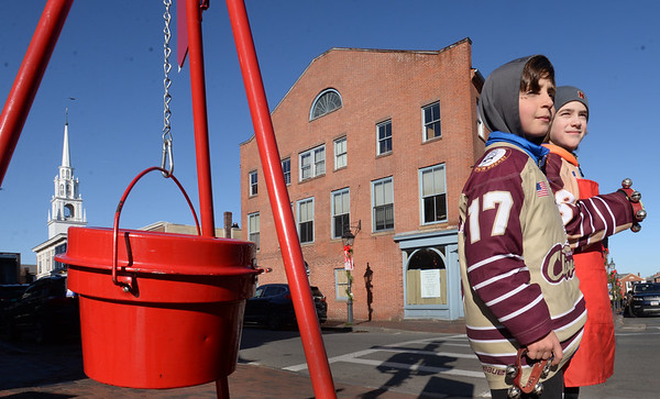 BRYAN EATON/Staff photo. Charlie Tramontana, left, and Thomas Duratti, both 10, man the kettle at the corner of State and Pleasant Streets in Newburyport. They and other teammates and coaches from Newburyport Youth Hockey's Squirt 1 Team were looking for a way to give back to the community so they decided to collect donations for the Salvation Army.