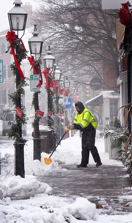 BRYAN EATON/Staff Photo. Tom  Graham of New England Development cleans off the sidewalk on Pleasant Street in Newburyport during the seasons first snow storm on Monday morning.