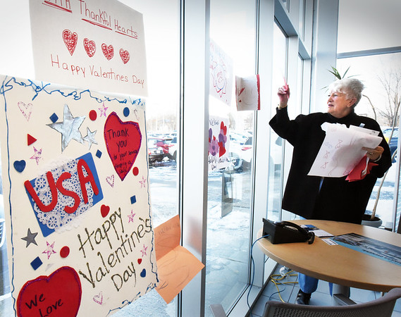 BRYAN EATON/Staff photo. Rosemary Werner, who founded the Heart to Heart project several years ago, removes larger Valentine cards that were on disply to be distributed to Massachusetts veterans hospitals.
