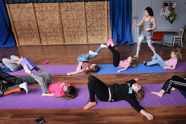 BRYAN EATON/Staff photo. Youngsters under the supervision of Elissa Shoreman do one excercise where they use only their feet to transport a box to each other. The yoga instructor from Rowley teaches the class at the Boys and Girls Club in Salisbury on Wednesdays.