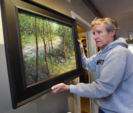 """BRYAN EATON/Staff photo. Jay McCarthy hangs the Sam Sargent Best in Show, a pastel by Tom Bailey titled """"Stepping Off Road."""""""