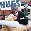 BRYAN EATON/Staff photo. Kerri Morrison of Newburyport, and owner of Awaken Holistic Counseling Services in downtown Newburyport, gives a hug to passerbyer Larry Sostak of Newburyport on Wednesday afternoon. When she was in college she learned about an Australian man who started the campaign to offer hugs to strangers in public places. The hugs are meant to be random acts of kindness—selfless acts performed just to make others feel better.