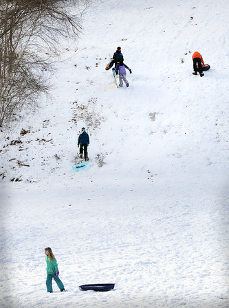 BRYAN EATON/Staff photo. Youngsters head up March's Hill in Newburyport on Monday morning for some sleddding. Today could be the last day of sledding unless another storm dumps some snow as today and tomorrow could make records for warm weather.