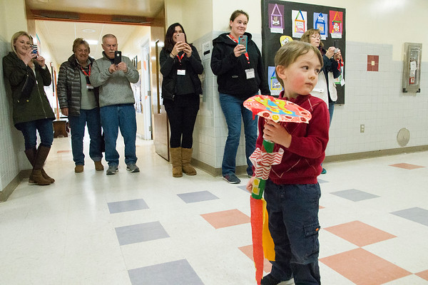 JIM VAIKNORAS/Staff photo Connor Borgatti leads his classmates in a Dragon Parade past a gauntlet of cell phone wielding family members during a Chinese New Year celebration at Newbury Elementary School Friday. Connor is a student is Mary Jo Lagana's pre-school class. Along with the parade the kids sang songs and eat rice balls, noodles and fruit.