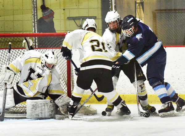 BRYAN EATON/Staff photo. Haverhill goalie Shane Corbett gets help from his defense as Triton's Sam Rennick tries to put in the puck.