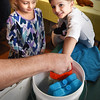 BRYAN EATON/Staff photo. Kyle Lachendro, 6, of Georgetown, right, and Kaitlyn Foster, 6, of Newburyport took turns putting their hands in ice water then here repeated it, though this time with their hands in a double-lined glove, guided by Tim Booth, filled with solid food shortening. They were at one of several programs this week at the Joppa Flats Education Center, this one on pennipeds--which include seals and sea lions--which shows how layers of fat protect them from cold water.