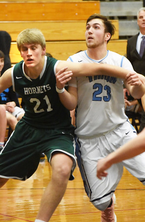 BRYAN EATON/Staff photo. Manchester-Essex player Colton Tosi and William Parson angle for a rebound.