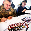 BRYAN EATON/Staff photo. Area emergency personnel, politicians, community members, active and retired military converged at Amesbury Chevrolet to write Valentine cards for area veterans who live at home and those who are in VA hospitals, part of the Heart to Heart program. Writing cards for veterans who live at home are reserve US Army Ssgt. Joseph LeBlance of Amesbury and retired US Navy veteran Hank Cross of Merrimac. School children in are towns created the cards that are to be delivered to the VA Hospitals in Massachusetts.