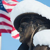 JIM VAIKNORAS/Staff photo The flag waves behind a snow covered Doughboy Statue at Amesbury Middle School Sunday morning.