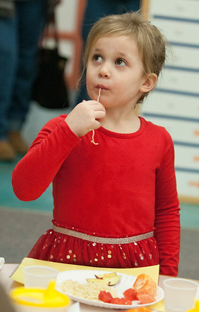 JIM VAIKNORAS/Staff photo Rose Rice enjoys some noodles during a Chinese New Year celebration at Newbury Elementary School Friday. Rose is a student is Mary Jo Lagana's pre-school class. Along with the food the kids had a Dragon Parade and sang New Years songs.