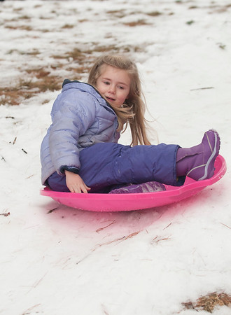 JIM VAIKNORAS/Staff photo Hadley Aslin, 4, sleds on a plastic saucer at the annual West Newbury Winter carnival at Mill Pond Saturday.Along with sledding, the event included skating, hockey, food, music and a visit from Frosty and the Cat in the Hat.