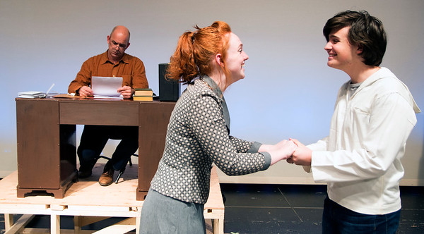 """JIM VAIKNORAS/Staff photo Joe Poirier, as Mr Woodwell, reads letter as Hannah Rowe greets Quinn Eckelkamp in the Amesbury High production of """"Dear Mr. Woodwell."""