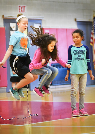 BRYAN EATON/Staff photo. Students from Londonderry Elementary School in New Hampshire have a jump rope team named the Hip Hoppin' Hawks that perform and spread the positive health message about fitness and nutrition. They were at Cashman Elementary School to get the students ready for their upcoming Jump Rope For Heart event coming up.  Hawk's Paige Dobe, left, gets Cashman students into the act, Lavinia Minkowski, 9, jumping as Meah Brown, 6, awaits her turn.