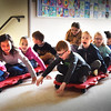 BRYAN EATON/Staff photo. Cashman School in Amesbury held their own Olympic Games with opening ceremonies on Friday morning. Here, one class does the bobsled, taking turns at other events as the snowflake toss, floor hockey and curling.
