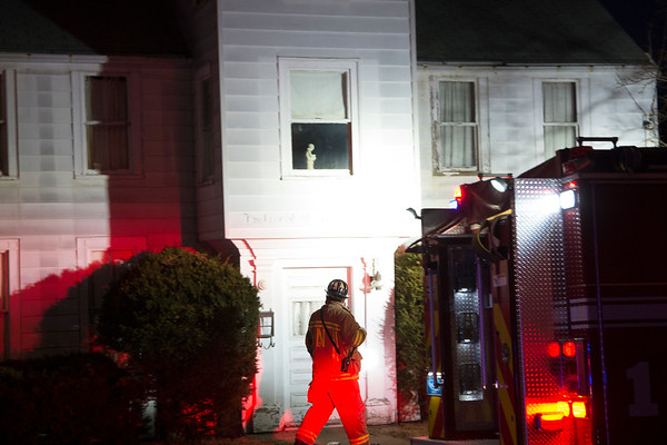 JIM VAIKNORAS/Staff photo A Newburyport firefighter checks the front of a house on Merrimac Street between Woodland and Howard Wednesday night.