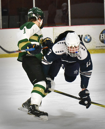BRYAN EATON/Staff photo. Hamilton-Wenham defenseman Luke McClintock takes a spill colliding with Pentucket's Hazen Pike.