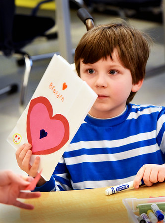 BRYAN EATON/Staff photo. Braeden Farrell, 6, shows off his Valentine bag to fellow first-graders in Mary Ahern's class at the Bresnahan School on Tuesday afternoon. They were making the bags for Valentine cards to be passed out among classmates today.